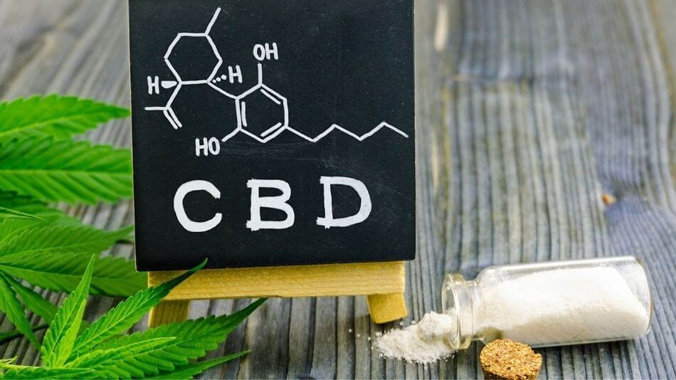 A bottle of CBD isolate powder laying on its side with some pouring out and a chalkboard with the CBD molecule drawn on it.