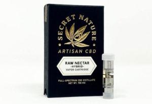Secret Nature Raw Nectar Full Spectrum CBD vape cartridge standing upright next to its box.