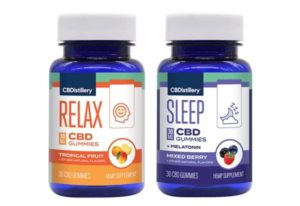 A bottle of CBDistillery tropical fruit and mixed berry CBD gummies standing side by side.